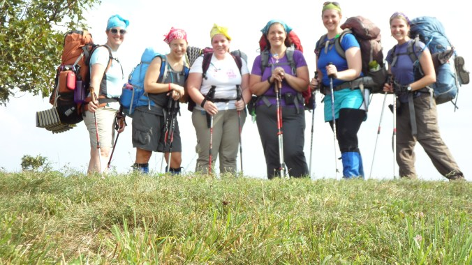 six hikers wearing backpacks and carrying hiking poles